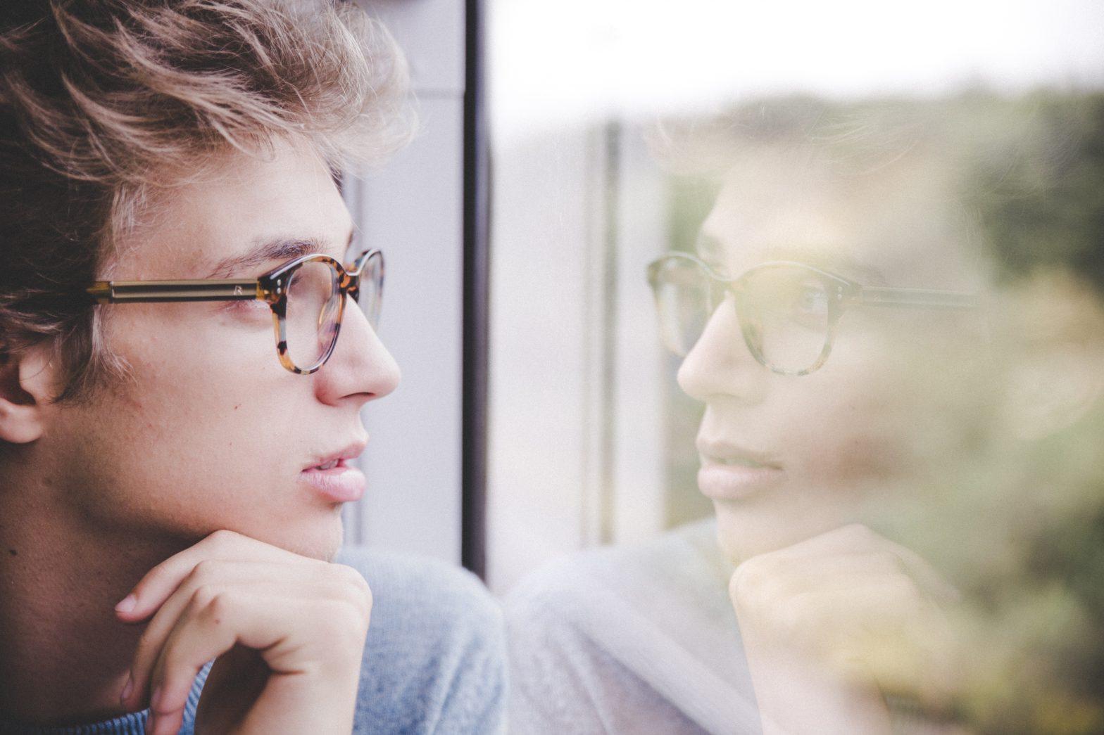 Men looking at window thinking